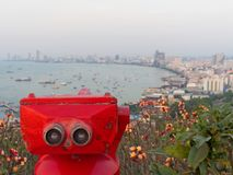 Red binocular on Pattaya beach showing explore and discover new place in tourism industry. With sky, sea, and coast on background Royalty Free Stock Image