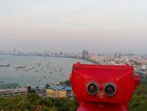 Red binocular on Pattaya beach showing explore and discover new place in tourism industry. With sky, sea, and coast on background Royalty Free Stock Photos