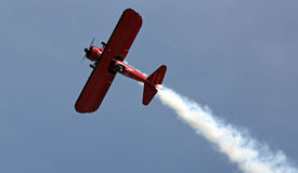 Red Biplane at EAA AirVenture Airshow. A bright red biplane performs aerobatics at the 2016 EAA AirVenture airshow in Oshkosh, Wisconsin stock photos