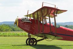 Red Biplane with OX-5 Engine. Red biplane, a Curtiss JN-4 Jenny parked in a grass field showing an OX-5 engine, bracing wires, interplane struts, cabane struts stock images