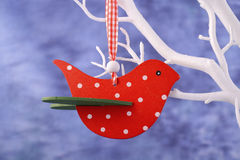 Red bird ornament hanging from white branch. Stock Image