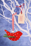 Red bird ornament hanging from white branch. Royalty Free Stock Photo