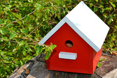 Red birdhouse with white roof, sitting on a log. stock images