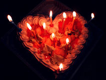 Red Birthday cake in the form of heart with candles. royalty free stock images
