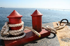 Red Bitts On A Jetty. Thick rope around metallic bitts on a  jetty in Guanabara Bay, Rio de Janeiro, Brazil. Rio-Niteroi bridge in background Royalty Free Stock Photos