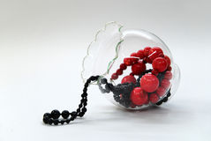 Red and black beads in a glass bowl. Red and black shining beads in a glass bowl Stock Photography