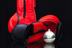 Red and black boxing gloves and Christmas decoration. On black glass table. Christmas is not a struggle for Christmas gifts Stock Photography