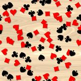 Red and black card symbols on the wooden table - seamless pattern background Stock Photos