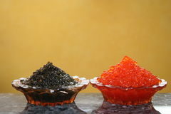 Red and black caviar. It is a lot of red and black caviar in a plate on a table Stock Photo