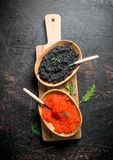 Red and black caviar in the bowls on the cutting Board. On dark rustic background stock images