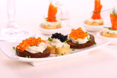 Red and black caviar on bread chunks as snack Stock Image