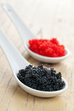 Red and black caviar in ceramic spoon Royalty Free Stock Photography