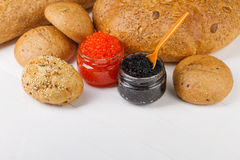 Red and black caviar in a jar with bread Stock Images