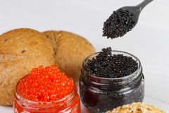 Red and black caviar in a jar with bread Royalty Free Stock Photography