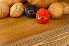 Red and black caviar in a jar with bread Stock Image