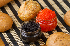 Red and black caviar in a jar with bread Royalty Free Stock Photo