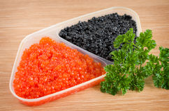 Red and black caviar is in a serving plate. On a wooden table Stock Image