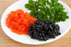 Red and black caviar is in a serving plate. On a wooden table Stock Images