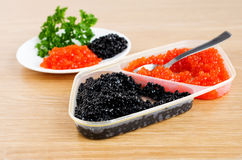 Red and black caviar is in a serving plate. On a wooden table Royalty Free Stock Photos
