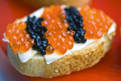 Red And Black Caviar Snack. There are stripped red and black caviar with butter and white french bread on a red plate Stock Images