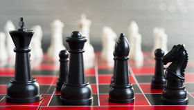 Red Black Chess Board Game Pieces King Queen Bishop Knight. An inexpensive Chess board stans red against white Stock Photography