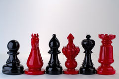 Red and Black Chess Pieces. Chess pieces in a line alternating colors Royalty Free Stock Photography