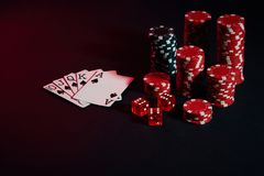Red and black chips for gambling and playing cards on black background. Still life. The concept of gambling. Poker Online. Copy space. Ideal for advertisement stock photo