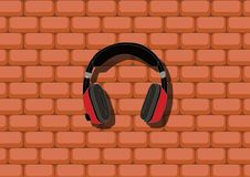 Headphones in front of the wall. Red-black circumaural headphones hangs in front of the brick wall; minimalistic concept Royalty Free Stock Photos