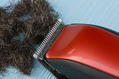 Red black clipper and a bunch of hair on a blue table. Electric hair clipper and cut hair on a blue background stock images