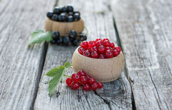 Red and black Currants. Fresh ripe organic red and black currants with green leaf in a wooden bowl on the rustic wooden table. Closeup with copy space Royalty Free Stock Photography