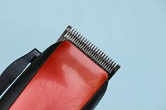 Red black hair clipper on a blue background Royalty Free Stock Photography