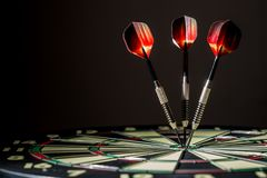 Profile of Dartboard with Three Bulls eyes. Red, black, and green dartboard on its side with three fiery metal tipped darts in the bulls eye. On black background Stock Image