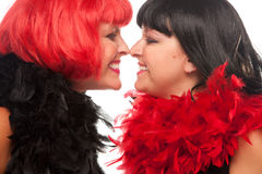 Red and Black Haired Women Smiling at Each Other Stock Photo