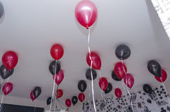 Red and black inflatable balls under the white ceiling Royalty Free Stock Images