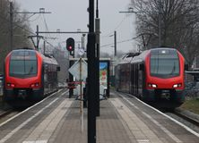 Red black local commuter train is arriving at the both sides of. The station of Waddinxveen, the netherlands royalty free stock photo
