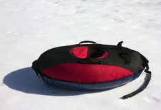 Red and black material snow inner tubing (toobing) on the white Royalty Free Stock Photography