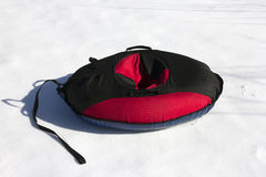 Red and black material snow inner tubing on the white Royalty Free Stock Image