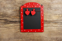 Red and black memo board with clothes pegs in heart shape Royalty Free Stock Photo