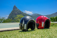 Red and black motorcycle helmets lying on the grass on the background of the statue of Christ the Redeemer. In Mirante Dona Marta, Tijuca Forest, Rio de Janeiro Stock Images
