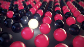 Red, black and one illuminated sphere aligned in a row Royalty Free Stock Photography