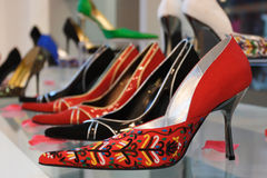 Red, black and others spike heel on glasses shelf. On photo red, black and others spike heel on glasses shelf Stock Photography