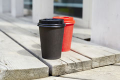 Red and black paper cups of coffee to takeaway on wooden floor outside the cafe. Breakfast morning on air. Stock Images