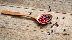 Red and black pepper in the spoon on the table Royalty Free Stock Photography
