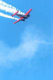 Red and black plane high in the sky Stock Image