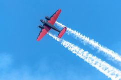 Red and black plane high in the sky. I captured this image at an Air Show in Waterloo, Iowa in August of 2014. This plane once used to haul executives from place royalty free stock photography