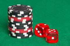 Red and black poker chips and dice on a green casino felt Royalty Free Stock Photos