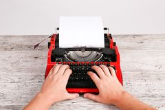 Red and black retro typewriter with white blank paper sheet on the wooden table table. Top view of the white man prints on red and black retro typewriter with Royalty Free Stock Photos