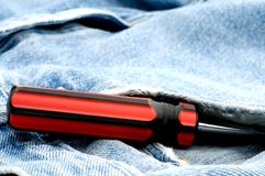 Red and black screwdriver in jeans pocket Stock Photography