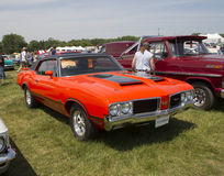 1972 Red with black stripes Olds Cutlass Side View. IOLA, WI - JULY 13:  Side of 1972 Red with black stripes Olds Cutlass Car at Iola 41st Annual Car Show July Royalty Free Stock Image