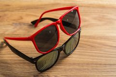 Red and black sunglasses on a table Royalty Free Stock Images